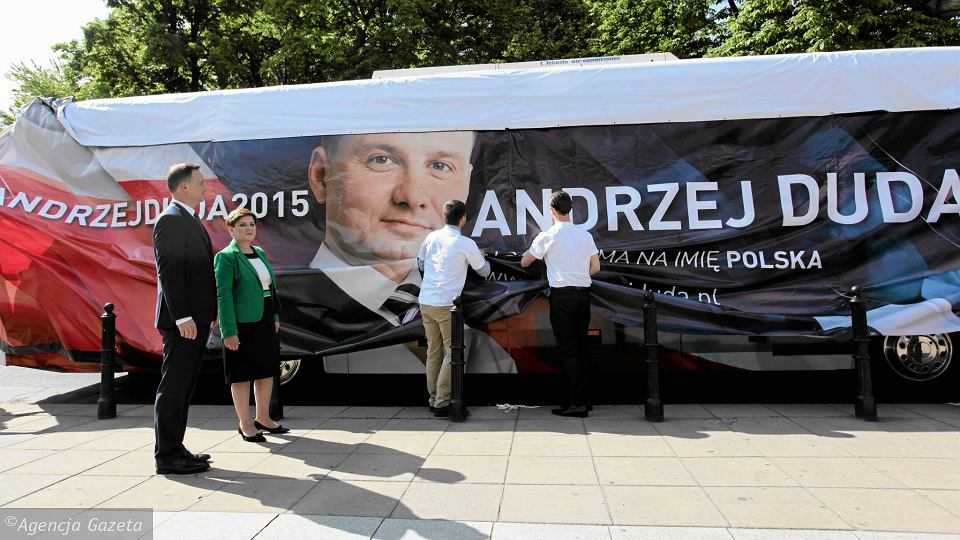 Prezydent elekt Andrzej Duda i kandydatka PiS na premiera Beata Szydło obserwują, jak dudabus przeobraża się w szydłobus