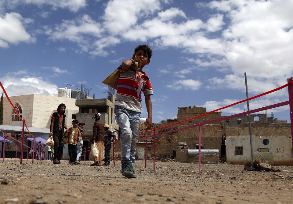 Młody mieszkaniec Sany po odebraniu żywności z punktu pomocowego
