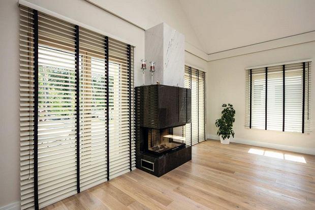 Białe żaluzje w salonie optycznie powiększą pomieszczenie: model drewniany to HIT
