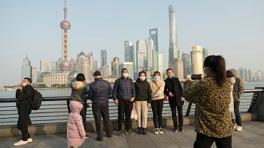 30.01.2020 Szanghaj. Turyści w ochronnych maseczkach, pozują do zdjęcia na tle wieżowców.