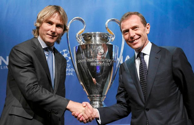 Juventus' ambassador Pavel Nedved (L) shakes hand with Real Madrid's ambassador Emilio Butragueno in front of the trophy after the draw for the Champions League semi-finals matches at the UEFA headquarters in Nyon, Switzerland, April 24, 2015. Barcelona will play against Bayern Munich and Juventus against Real Madrid. The semi-finals will be played May 5, 6, 12 and 13 with the final June 6, 2015 in Berlin. REUTERS/Denis Balibouse SLOWA KLUCZOWE: :rel:d:bm:LR2EB4O0UQPTL