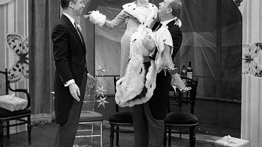 'Kaloryfeeria' z 30 stycznia 1960 r., czyli przypomnienie wieczoru IV 'Zbyteczne żeberko'. Pan B (Jeremi Przybora) i Pan A (Jerzy Wasowski) dźwigający Babkę Gołoledź (Barbara Krafftówna), czyli uroczą zimową panią, która twierdzi, że pojawiła się, żeby odciążyć trochę staruszka - Świętego Mikołaja.