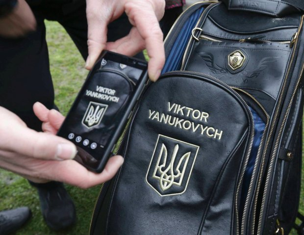 A man takes a picture of a golf bag as anti-government protesters and journalists walk on the grounds of the Mezhyhirya residence of Ukraine's President Viktor Yanukovich in the village Novi Petrivtsi outside Kiev February 22, 2014. Hundreds of people entered the grounds of Ukrainian President Viktor Yanukovich's sprawling residence outside Kiev on Saturday but had not gone inside the building itself, a Reuters photographer said. REUTERS/Konstantin Chernichkin (UKRAINE - Tags: POLITICS CIVIL UNREST) SLOWA KLUCZOWE: :rel:d:bm:LR2EA2M1KO2FD
