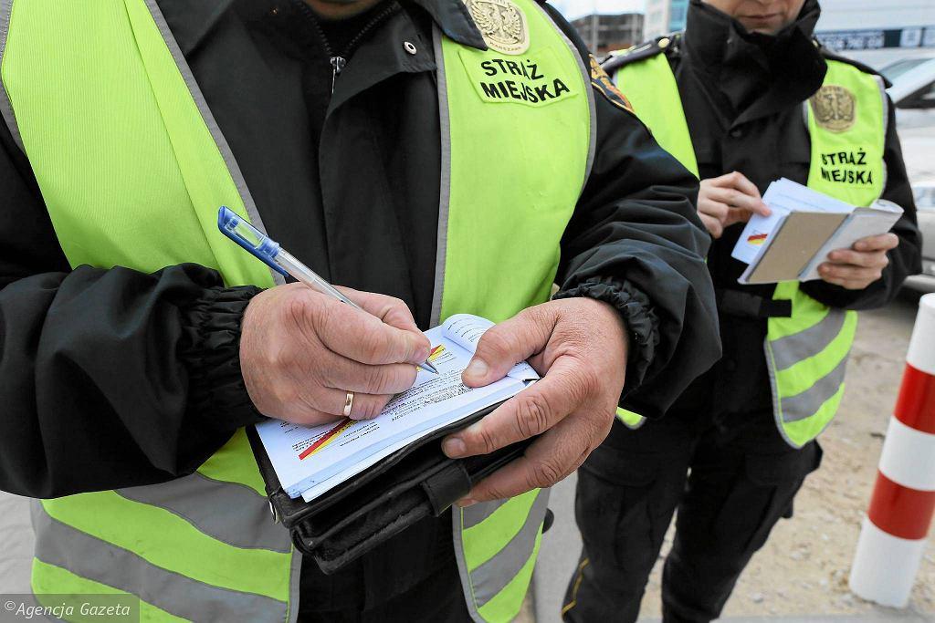 Strażnicy miejscy wypisują mandaty za złe parkowanie