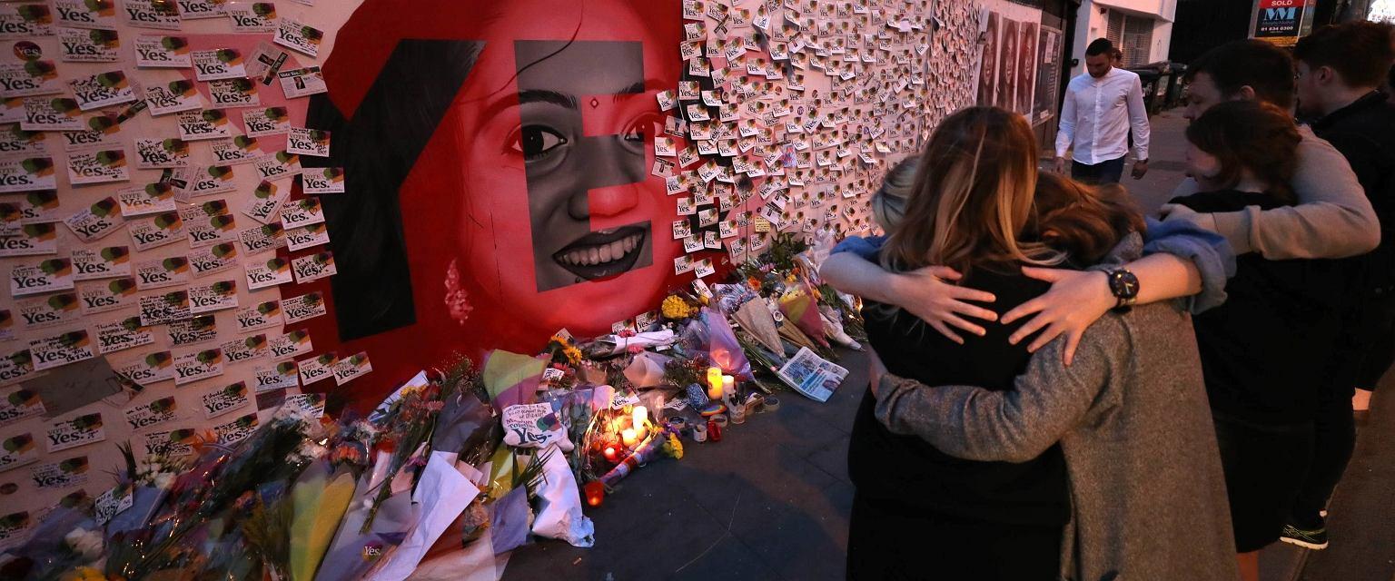 Ludzie kładą kwiaty i świece pod muralem upamiętniającym Savitę Halappanavar. Savita, której odmówiono aborcji, poroniła i zmarła na sepsę. Uznawana jest za ofiarę obowiązującego w Irlandii prawa aborcyjnego (fot. Niall Carson/PA via AP)