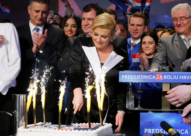 Kolinda Grabar-Kitarovic of the opposition HDZ cuts a cake as she celebrates her victory in Croatia's presidential run-off election on the stage at her campaign headquarters in Zagreb January 11, 2015. Croatia's conservative opposition won a narrow presidential victory on Sunday, capitalising on popular discontent over economic decline and setting down a marker for parliamentary elections later in the year. REUTERS/Antonio Bronic (CROATIA - Tags: POLITICS ELECTIONS)