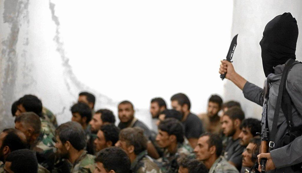 Bojówkarz Państwa Islamskiego grozi nożem pojmanym żołnierzom armii Syrii