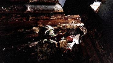 Ukraiński żołnierz z karabinem maszynowym w schronie w pobliżu miasta Krasnohoriwka we wschodniej Ukrainie.