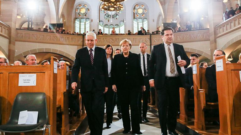 Flanked by the President of the Central Council of Jews in Germany Josef Schuster, left, and Gideon Joffe, right, head of the Jewish community in Berlin. German Chancellor Angela Merkel, center, arrive at the synagogue Rykestrasse at the district Prenzlauer Berg in Berlin, Friday, Nov. 9, 2018 for an event commemorating the Night of Broken Glass 1938, in which Nazis burned and vandalized synagogues and Jewish businesses across the country and killing over 400 people.
