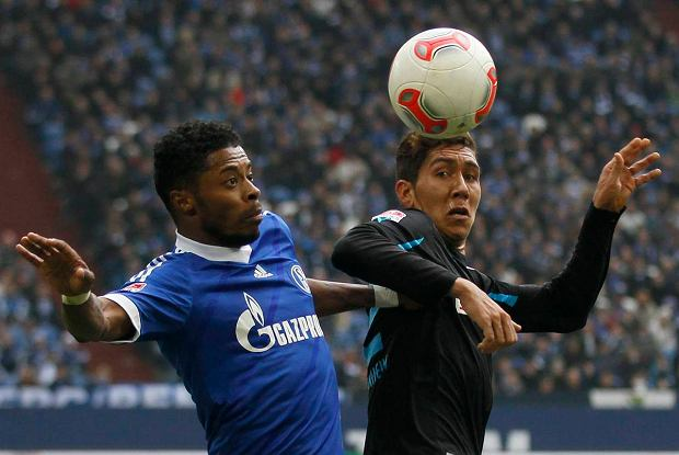 Michel Bastos of Schalke 04 (L) tackles Roberto Firmino of Hoffenheim during their German first division Bundesliga soccer match in Gelsenkirchen March 30, 2013.        REUTERS/Wolfgang Rattay (GERMANY - Tags: SPORT SOCCER) DFL RULES TO LIMIT THE ONLINE USAGE DURING MATCH TIME TO 15 PICTURES PER GAME. IMAGE SEQUENCES TO SIMULATE VIDEO IS NOT ALLOWED AT ANY TIME. FOR FURTHER QUERIES PLEASE CONTACT DFL DIRECTLY AT + 49 69 650050