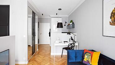 Malutkie wnętrze zostało podzielone. Projektantka zrezygnowała jednak z typowych ścian, które zabrałyby cenną przestrzeń - zamiast nich są szafy, niewysokie ścianki działowe i przesuwająca się zasłona.
