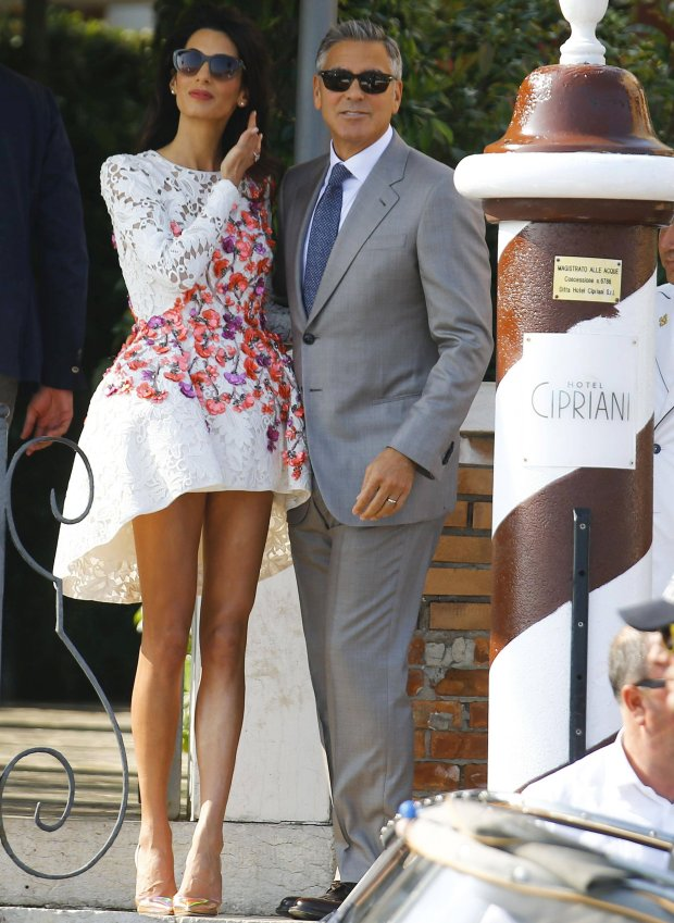 .U.S. actor George Clooney and his wife Amal Alamuddin arrive at the Cipriani hotel in Venice September 28, 2014. The worlds most famous bachelor broke a vow to remain single on Saturday and married human rights lawyer Alamuddin during a weekend of lavish celebrations in Venice. The Italian city of gondolas and palazzi looked like Hollywood on the Adriatic as A-list guests cruised between luxury hotels for the extravaganza, billed as the party of the year even as details were kept largely secret. REUTERS/Stefano Rellandini (ITALY - Tags: ENTERTAINMENT)