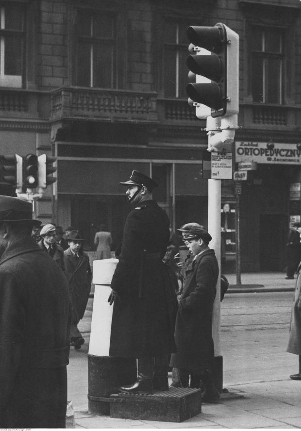 Warszawa, listopad 1938 r. Pierwszą sygnalizację świetlną w Polsce zamontowano w 1927 r. i miała tylko dwa kolory: czerwony i zielony. Po kilku latach. zlikwidowano zielone światło (czerwone - 'stój', brak światła - 'jedź'), ale szybko to zarzucono i tuż przed wojną sygnalizacja świetlna w Warszawie wyglądała już niemal tak samo jak współczesna.  Na zdjęciu sygnalizator na skrzyżowaniu ul. Marszałkowskiej z Sienkiewicza i Sienną.