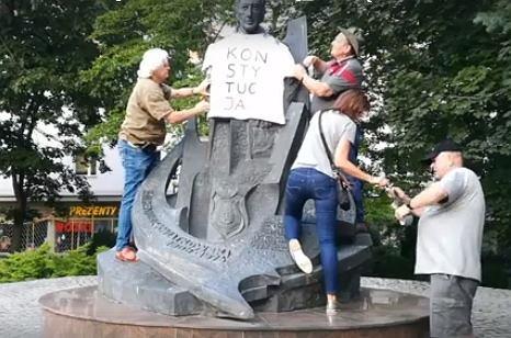 Stalowa Wola. Wieszanie koszulki z napisem 'Konstytucja' na pomniku