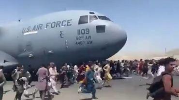 Ludzie biegnący po pasie kabulskiego lotniska obok startującego C-17 lotnictwa USA