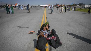 Afganistan. Kobiety i dzieci siedzą na pasie startowym lotniska w Kabulu czekając na samolot