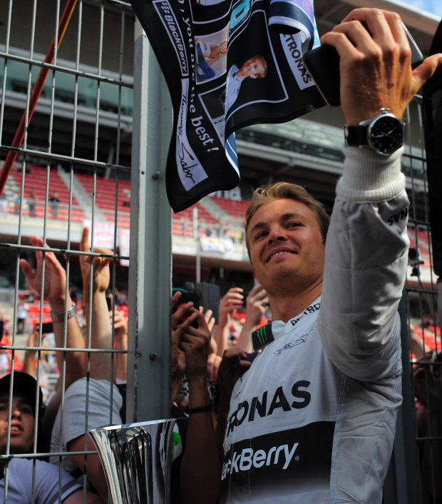 Mercedes driver Nico Rosberg of Germany makes a 'sefie' picture next to supporters as he celebrates his second position at the end of the Spain Formula One Grand Prix at the Barcelona Catalunya racetrack in Montmelo, near Barcelona, Spain, Sunday, May 11, 2014. (AP Photo/Manu Fernandez)
