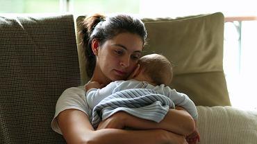 Zmęczona matka trzyma na rękach dziecko
