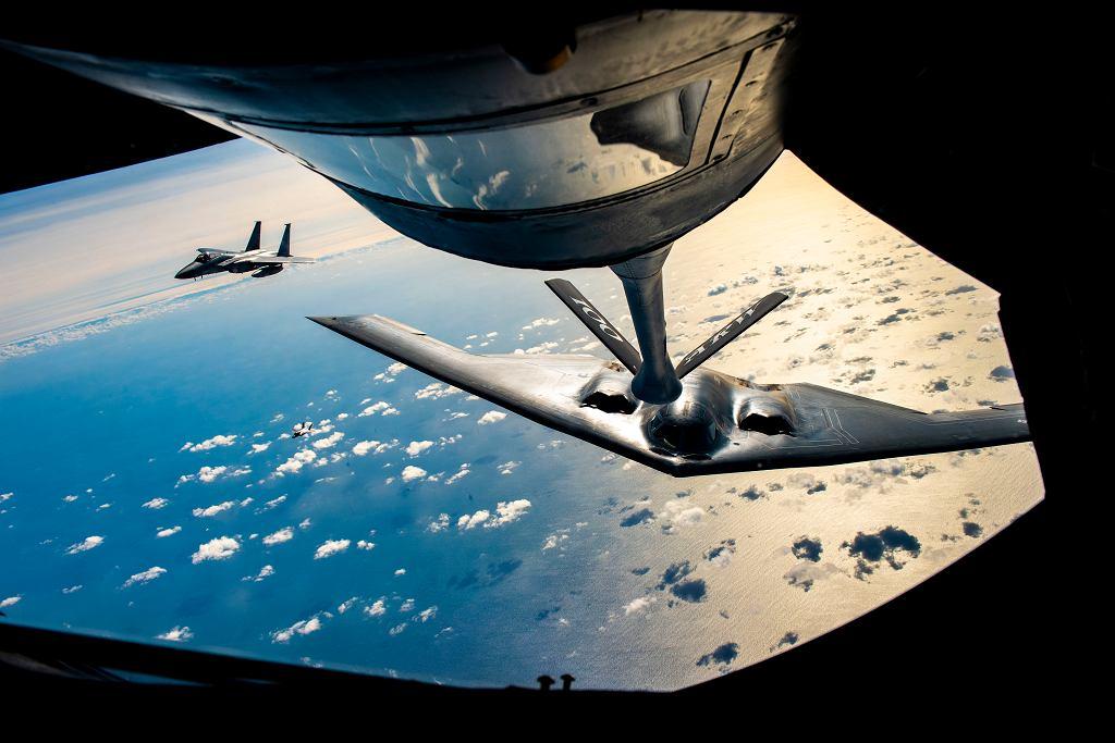 Bombowiec strategiczny B-2 podczas przygotowania do powietrznego tankowania. Obok myśliwiec F-15