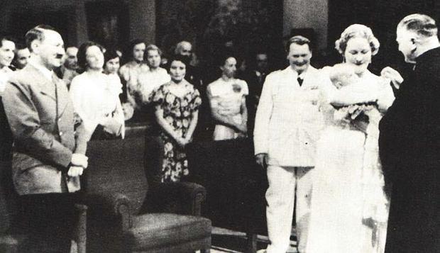 Kościelny chrzest Eddy Göring rozgniewał wielu nazistowskich hierarchów, ale to nie powstrzymało Hitlera przed uczestnictwem w ceremonii. Promieniejący Göring ma na sobie swój paradny biały mundur.