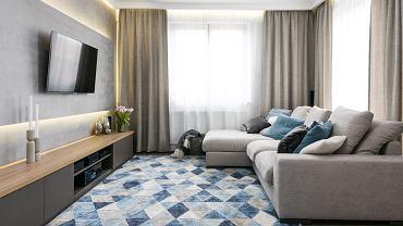Strefa dzienna wypełniona jest naturalnym światłem dzięki dużym oknom. Wrażenie to potęgują podłogi z jasnego drewna i ściany pomalowane na jasno-szary kolor. Graficzne akcenty i niebieskie poduchy ożywiają monochromatyczną stylizację.