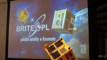 Model polskiego satelity BRITE Heweliusz eksponowany w Centrum Hewelianum na tle wizualizacji projektu BRITE-PL, w dniu udanego wystrzelenia na orbitę 19.8.2014