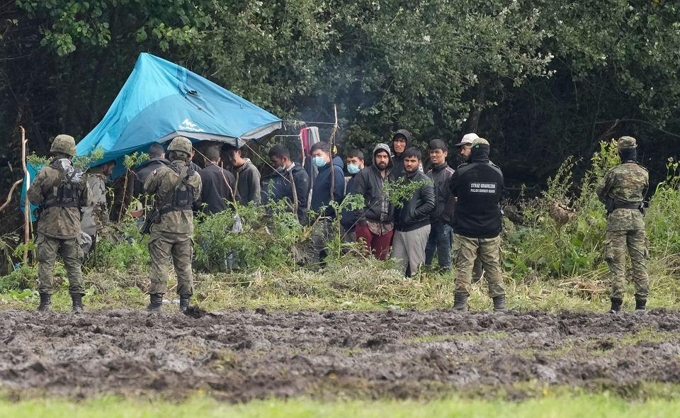 Polscy żołnierze pilnują uchodźców, którzy utknęli w Usnarzu Górnym przy granicy z Białorusią, 1 września 2021 r.