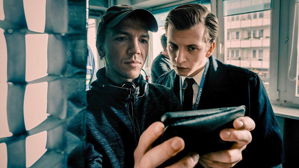 Jan Komasa na planie swojego najnowszego filmu 'Sala samobójców. Hejter'. Reżyser pokazuje aktorowi Maciejowi Musiałowskiemu coś na ekranie swojego telefonu.