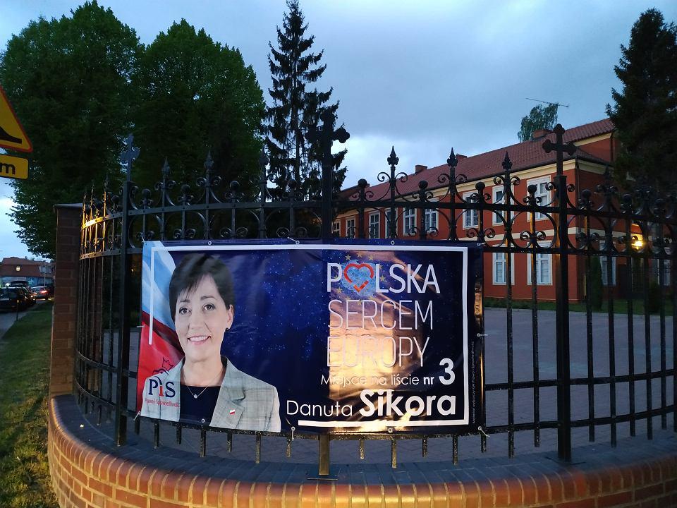 Kandydatka PiS Danuta Sikora reklamuje się na płocie parafii, tuż przy rezydencji, w której mieszka abp. Sławoj Leszek Głódź. W tle budynek parafialny, dworek arcybiskupa znajduje się po lewej, na zdjęciu zasłaniają go drzewa
