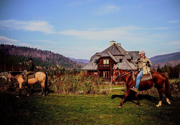 Piotr Tuniewicz demonstruje mi podstawy sztuki jazdy. W tle jego dom i stajnia.