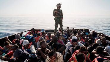 Libijski żołnierz straży przybrzeżnej na łodzi, która podjęła z pontonów imigrantów na zachód od Trypolisu, czerwiec 2017