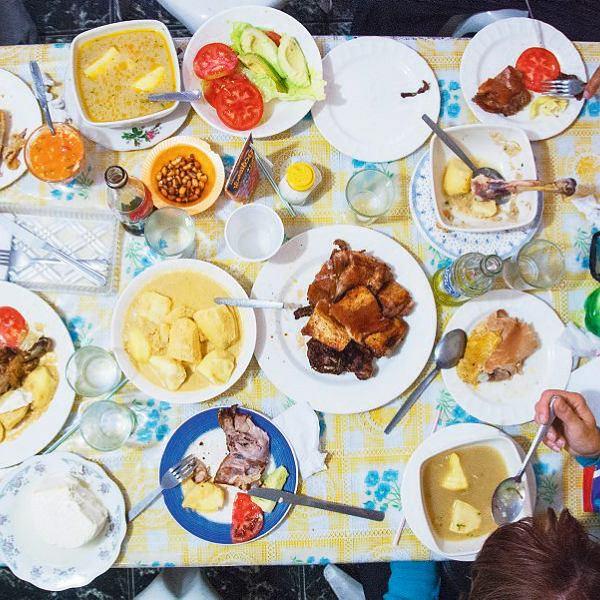 Na stole: pokrojone kawałki świnki morskiej (naśrodku), obok ziemniaki wsosie zorzeszków ziemnych izupa zkurczaka. Prażona kukurydza (tostado) oraz sałatka zpomidorów iawokado to dodatki dowiększości potraw; do tego biały ser, zupa zkrowich racic