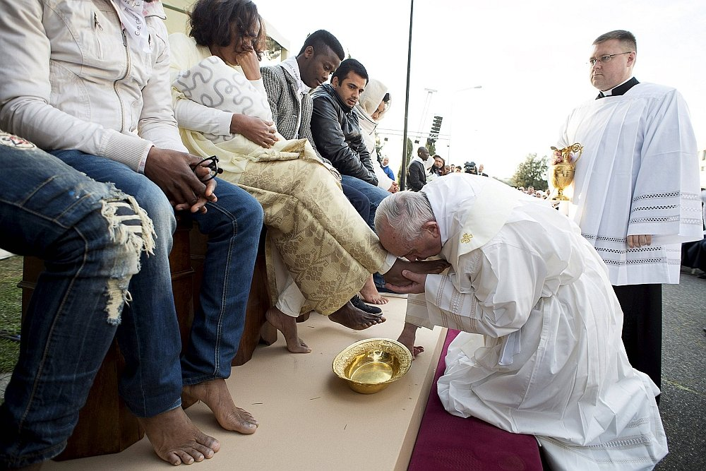 Papież Franciszek w tradycyjnym geście myje nogi uchodźcom