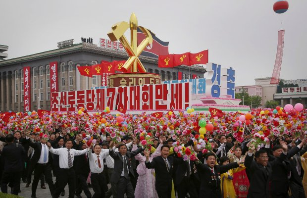 North Koreans march with the Workers' Party symbol and the words under it which read