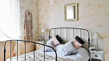SYPIALNIA. Kute łóżko wygląda jakby miało wiele lat i przyjechało z Prowansji. Tymczasem jest to model kupiony przed kilku laty w IKEA. Udało się do niego dobrać żyrandol w podobnym stylu. Jesionowe panele zostały pracowicie odnowione (w domu pani Jolanty poprzednio było biuro, więc podłoga była naprawdę zaniedbana).