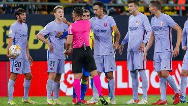 Referee Carlos Del Cerro Grande gestures after showing Barcelona's Frenkie de Jong, second left, a red card during a Spanish La Liga match.