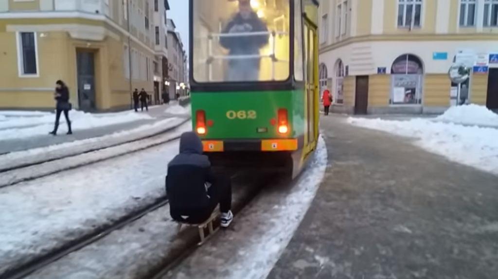 Mężczyzna jadący na sankach za tramwajem w Elblągu