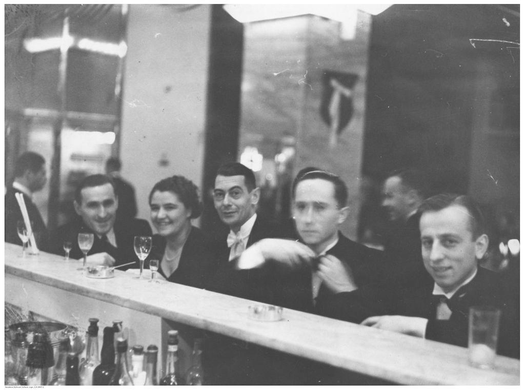 Grupa uczestników balu przy barze w Adrii. Od lewej widoczni, m.in.: lekkoatleta Janusz Kusociński, tenisistka Jadwiga Jędrzejowska oraz tenisista Ignacy Tłoczyński. Data wydarzenia: 1938-01-19.