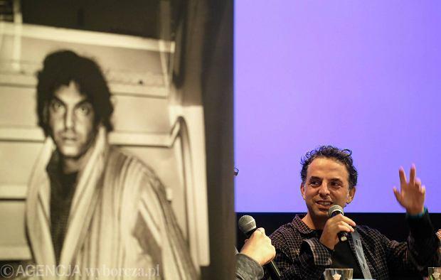 Etgar Keret podczas konferencji prasowej w barze Studio. Na pierwszym planie czarno-białe zdjęcie pisarza w szlafroku zrobione w najwęższym domu świata