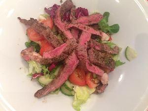 Sałatka z grillowaną w ziołach wołowiną, świeżymi sałatami, doprawiona malinowo-miodowym dressingiem
