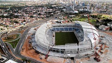 """<b>Arena das Dunas - Natal</b>. 42 000 miejsc, arena czterech meczów, koszt: 550 mln zł. To będzie prawdopodobnie najefektowniejszy stadion mundialu. Zdaniem tygodnika """"Veja"""" to najbardziej ekologiczny stadion Brazylii. W mieście Natal są dwa przyzwoite kluby; America i ABC, oba drugoligowe. Areną się podzielą. W przypadku Ameriki sprawa jest oczywista, bo nowy obiekt stanął na miejscu ich klubowego Machadao, ale ciekawostką jest dokooptowanie ABC. W 2006 roku klub postawił sobie własny stadion i wcale nie miał zamiaru grać gdzie indziej. Zarządca Areny das Dunas postanowił więc płacić klubowi za to, że ten 40 proc. meczów w lidze ogólnokrajowej będzie grał na mundialowym boisku. Ten kontrakt dla ABC wynegocjował jego prezydent, Tadeusz Juda, który imię i nazwisko dostał na cześć świętego od spraw trudnych i beznadziejnych"""