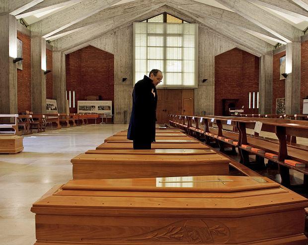 Ksiądz Mario Carminati w kościele wypełnionym trumnami