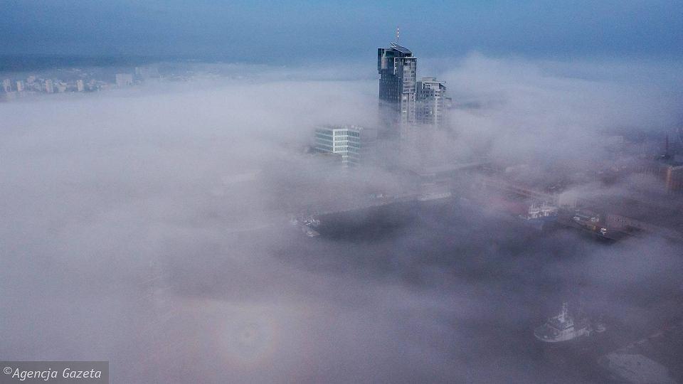 Gdyński waterfront. Z mgły wyłaniają się wieże Sea Towers. Tuż obok biurowiec i hotel otwarte w tym roku. Za nimi w przyszłości powstanie kolejna zabudowa - usługowa, handlowa i kulturalna oraz mieszkania, skwery i pasaże