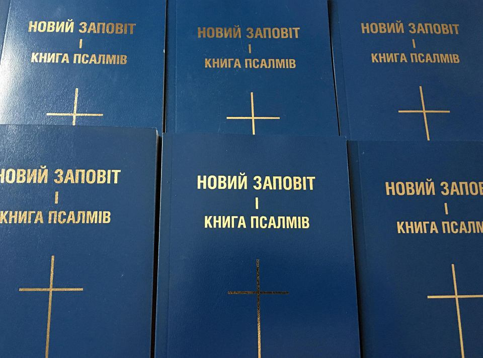 Ksiądz Byrt rozdaje Nowy Testament wydany w języku ukraiń