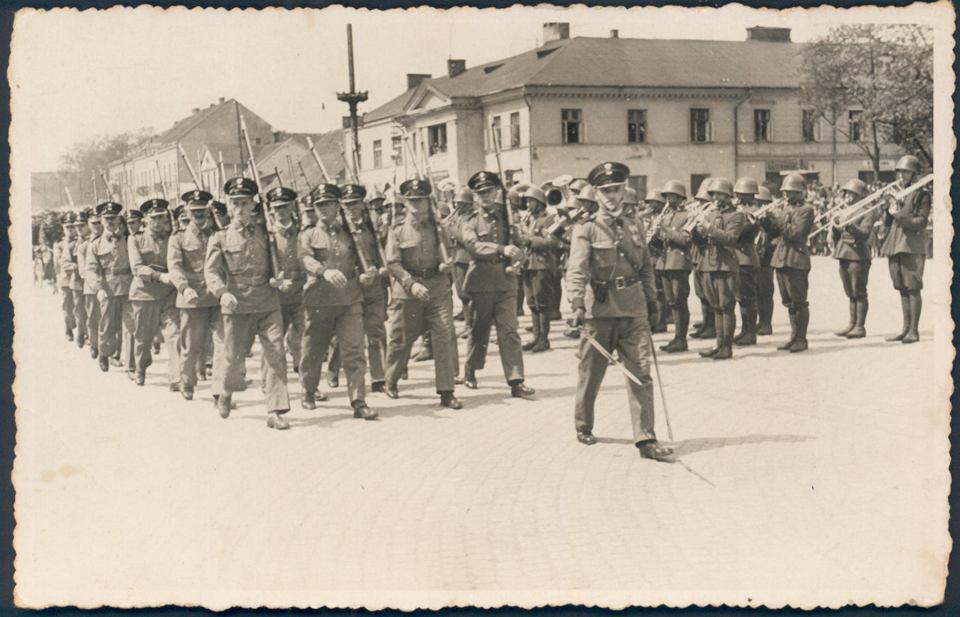 Częstochowa, plac Pierackiego (dziś Biegańskiego), 11 listopada 1938 r. Przed trybuną i orkiestrą 27. Pułku Piechoty defiluje zmilitaryzowane stowarzyszenie Strzelec stworzone na bazie dawnych legionistów. Prawdopodobnie są to pocztowcy. W tle nieistniejący budynek na rogu ul. Dąbrowskiego i III Alei mieszczący przeróżne instytucje, który został spalony 17 stycznia 1945 r. przez wkraczające wojska radzieckie
