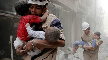 Członkowie obrony cywilnej ewakuują dzieci po nalocie wojsk wiernych al-Assadowi.