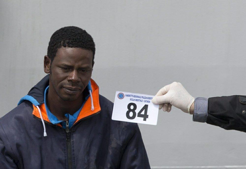 Nielegalni imigranci schodzą z włoskiego statku straży wybrzeża w porcie Catania na Sycylii