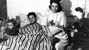 Warszawa, 2 sierpnia 1944 r., powstańczy szpital kompanii 'Koszta' przy ul. Moniuszki w Śródmieściu Północnym. Wśród rannych: sanitariuszka Janina Steczniewska 'Inka' z córką Hanią, pod kołdrą pchor. Edmund Michniewski 'Miś'