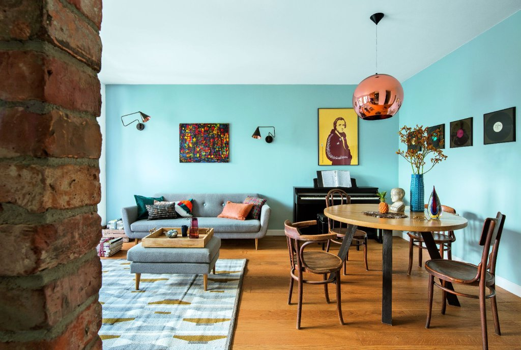 Obraz nad sofą był jednym z pierwszych elementów kupionych do tego mieszkania; do niego dopasowano kolorystykę detali. Stół zaprojektowała Patrycja Rabińska; krzesła pochodzą z rodzinnego domu Jakuba. Lampa Copper Shade (Tom Dixon).