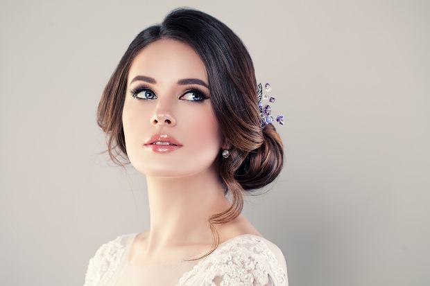 Luźno upięte koki to jedne z najmnodniejszych ślubnych fryzur, szczególnie z wpiętymi we włosy kwiatami czy naturalnymi ozdobami